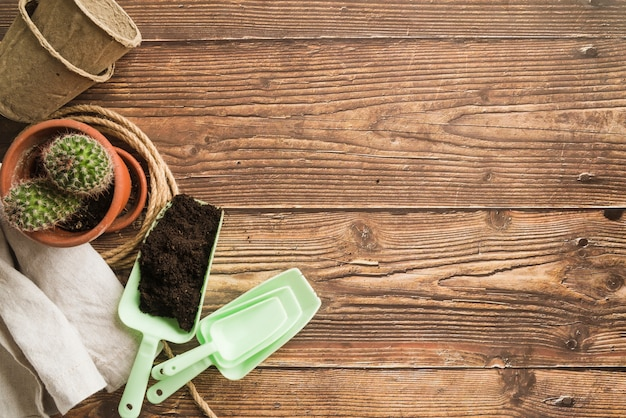 Soil; stacked of potted plant and napkin on wooden desk Free Photo