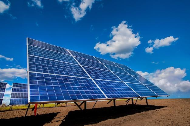 Панельная система солнечной энергии на вспаханном поле и небе с облаками Premium Фотографии