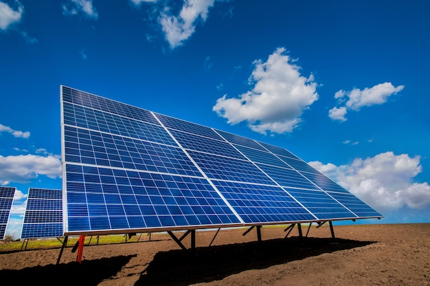 Solar energy station panel system on plowed field and sky with clouds Premium Photo