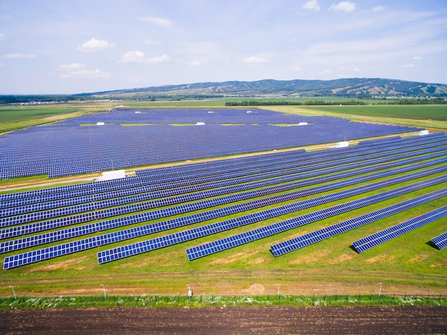 Solar panels on green grass with blue sky Premium Photo