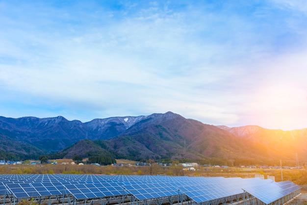 Solar panels (solar cell) in solar farm with blue sky and sun lighting. Premium Photo