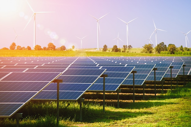 Solar panels and wind turbines generating electricity in power station green energy renewable with blue sky. natural resource conservation concept. Premium Photo