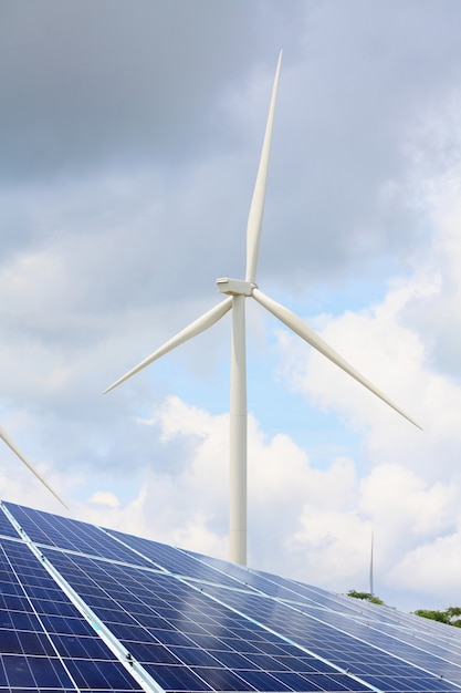 Solar panels and wind turbines with cloudy sky Premium Photo