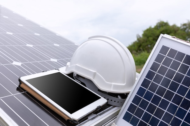 Solar photovoltaic panels station checks with tablet computer. Free Photo