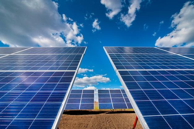 Панели солнечной электростанции, с отражением облаков и неба Premium Фотографии