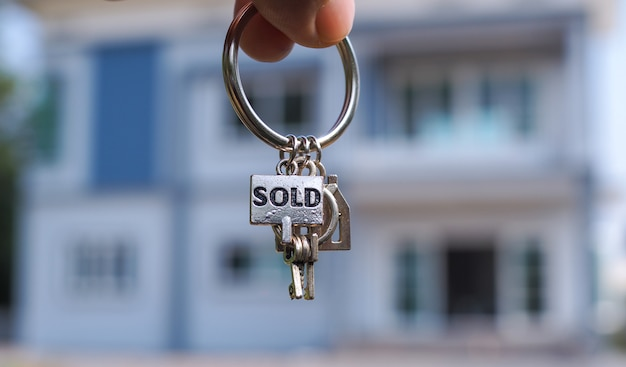 Sold house keys and blurry home Premium Photo