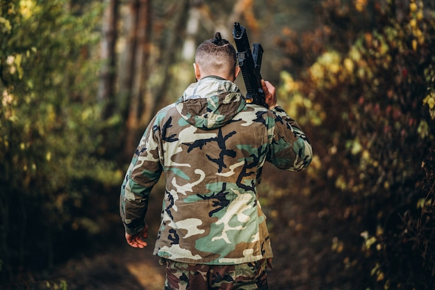 Soldier in camouflage uniform with a rifle on his shoulder walk in the forest. Premium Photo