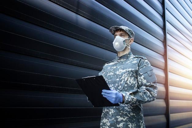 Солдат в камуфляжной форме в защитных перчатках и маске во время миссии против вируса короны Бесплатные Фотографии