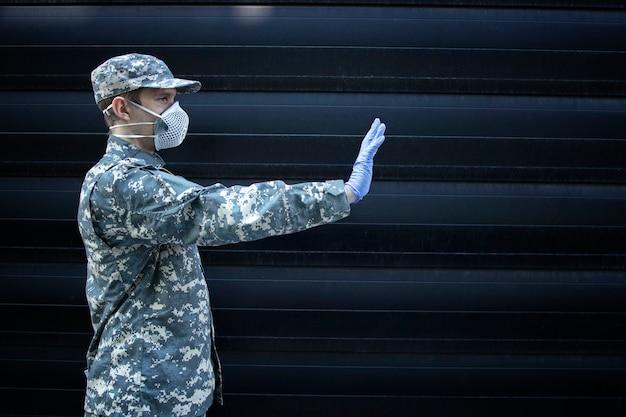 黒の背景に彼の手で一時停止の標識を示す保護手袋とマスクを身に着けているカモフラージュの制服を着た兵士 無料写真
