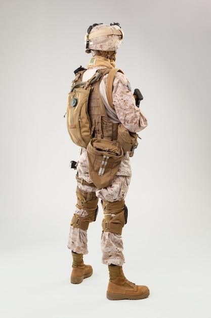 Soldier in us marines uniform with rifle on light grey background, studio shot Premium Photo
