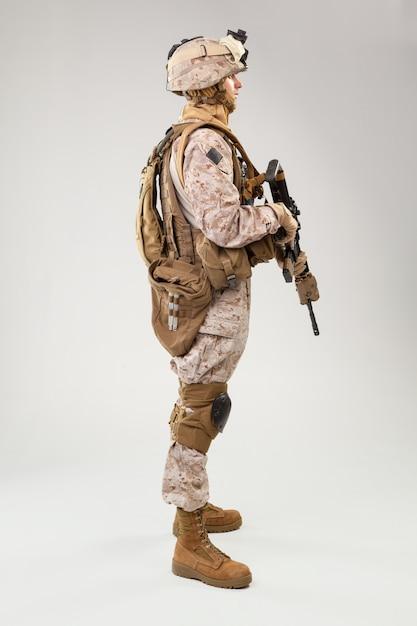 Soldier in us marines uniform with rifle on light grey , studio shot Premium Photo