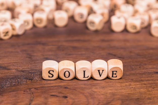 Solve word on wooden cubes over brown table Free Photo