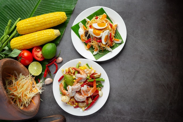 Som tum con mais e gamberetti, servito con spaghetti di riso e insalata verde decorato con ingredienti alimentari tailandesi. Foto Gratuite