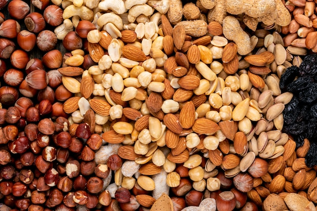 Some of assorted nuts and dried fruits with pecan, pistachios, almond, peanut, cashew, pine nuts top view. Free Photo