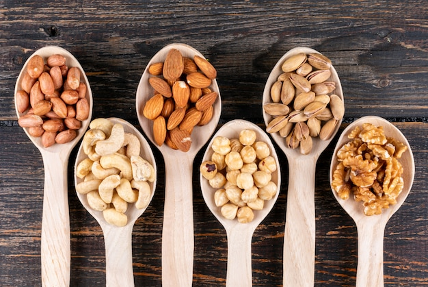 Some of assorted nuts and dried fruits with pecan, pistachios, almond, peanut, cashew, pine nuts in a wooden spoons Free Photo