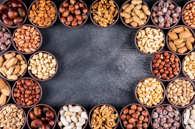 Some of assorted nuts and dried fruits with pecan, pistachios, almond, peanut, in a mini different bowls Free Photo