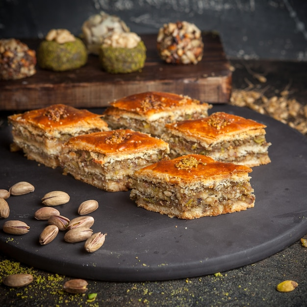 Some baklava with cookies on background on a black rounded platform side view. Free Photo