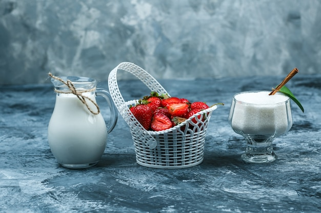 Some a basket of strawberries with a jug of milk and a glass bowl of yogurt on dark blue marble background, close-up. Free Photo