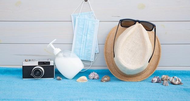 Некоторые пляжные аксессуары вместе с элементами защиты от коронавируса размещены на деревянной доске. Premium Фотографии