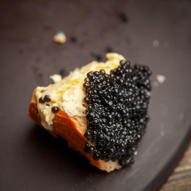 Un certo caviale nero con burro su pane su fondo scuro, vista dell'angolo alto. Foto Gratuite