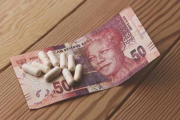 Alcune capsule su un 50 rand sudafricano su un tavolo di legno Foto Gratuite