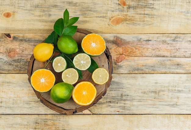 Some citrus fruits on a wooden board on wooden board Free Photo