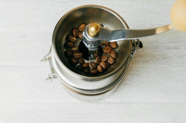 Несколько кофейных зерен в металлической кофемолке Premium Фотографии
