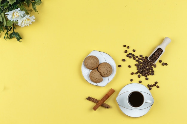 Some coffee with coffee beans, biscuits, cinnamon stick on yellow background Free Photo