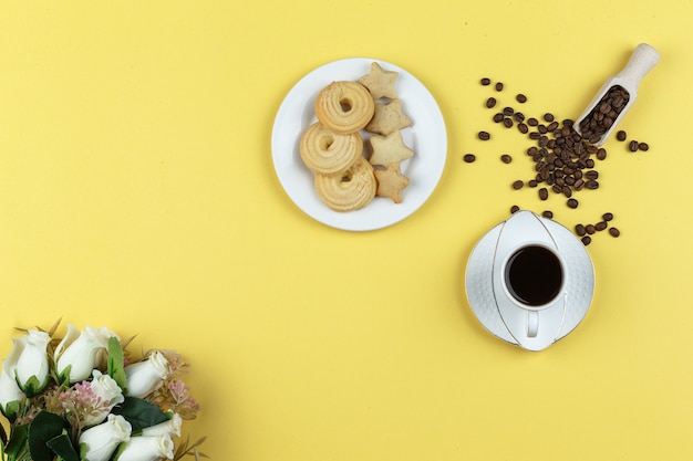 Some coffee with coffee beans and biscuits on yellow background Free Photo