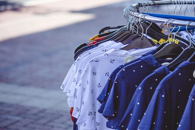 Разноцветные рубашки на вешалках на тротуаре Бесплатные Фотографии
