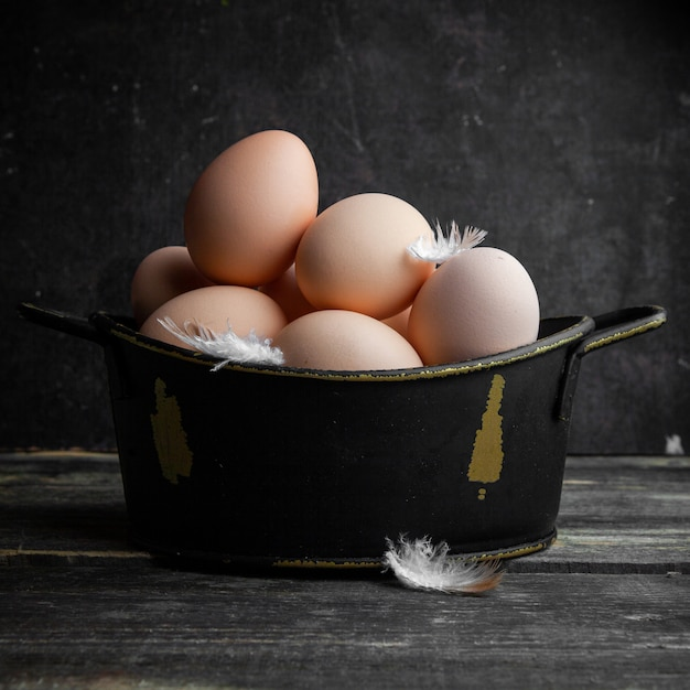 Some eggs with feathers in a pot on dark wooden background, side view. Free Photo