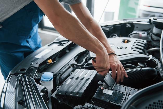 Alcune parti elettroniche. processo di riparazione dell'auto dopo l'incidente. uomo che lavora con il motore sotto il cofano Foto Gratuite