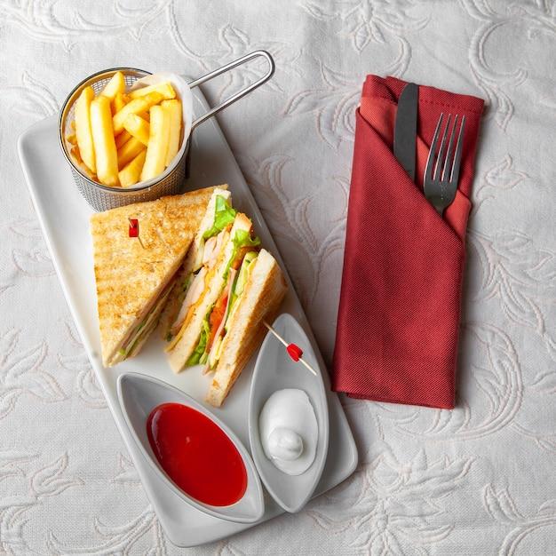 Alcuni alimenti a rapida preparazione con il panino, le patate fritte, la forcella e la lama su priorità bassa strutturata bianca, vista superiore. Foto Gratuite