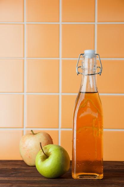 Alcune mele fresche con il succo di mele in un canestro sul fondo arancio delle mattonelle, vista laterale. spazio per il testo Foto Gratuite
