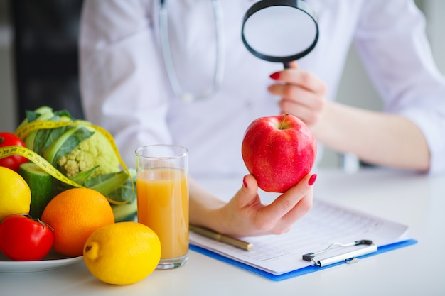 Some fruits such as apples, kiwis, lemons and berries on nutritionist table Premium Photo