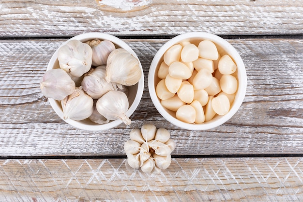 Some garlic in a bowls and nearby on wooden table, top view. Free Photo