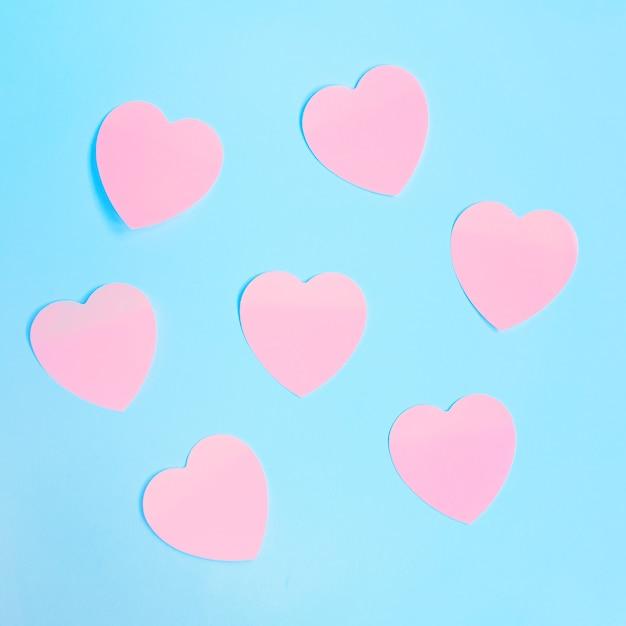 Некоторые в форме сердца розовые липкие заметки на синем фоне. день святого валентина, концепция любви. Premium Фотографии
