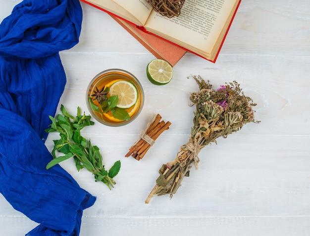 Alcuni tè alle erbe e fiori con libri, limone, spezie e sciarpa blu sulla superficie bianca Foto Gratuite