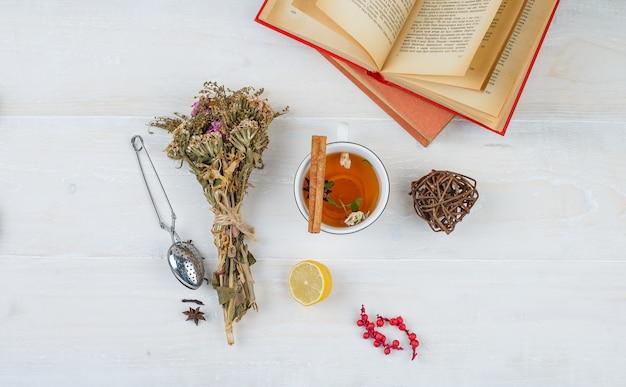 Alcuni tè alle erbe e fiori con libri, limone, colino da tè e spezie sulla superficie bianca Foto Gratuite