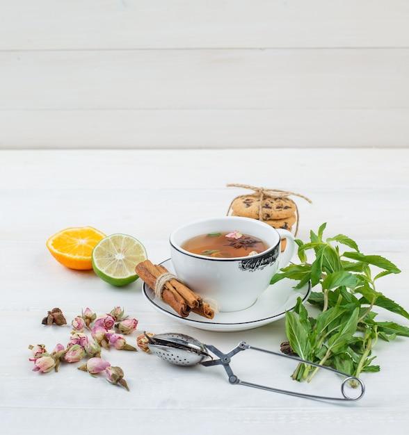 Alcune tisane con colino da tè, erbe aromatiche, agrumi e biscotti Foto Gratuite