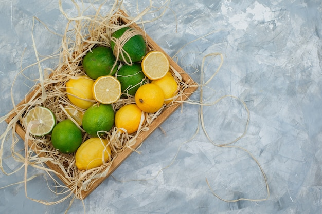 Некоторые лаймы и лимоны с деревянным ящиком на серой и синей мраморной поверхности Бесплатные Фотографии