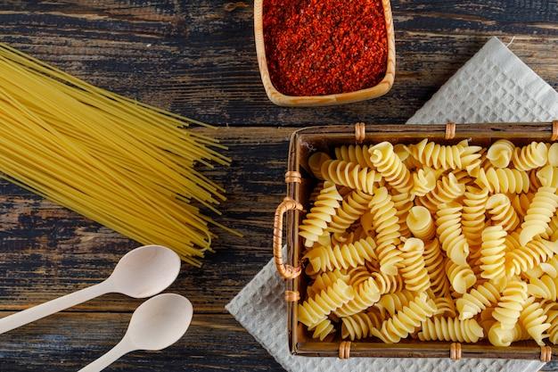 Некоторые макароны макароны с спагетти, ложки в лотке на деревянных фоне, вид сверху. Бесплатные Фотографии