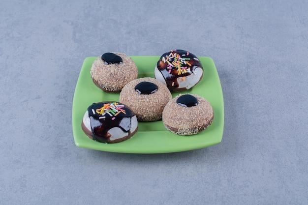 녹색 접시에 뿌리와 신선한 초콜릿 도넛의 일부. 무료 사진