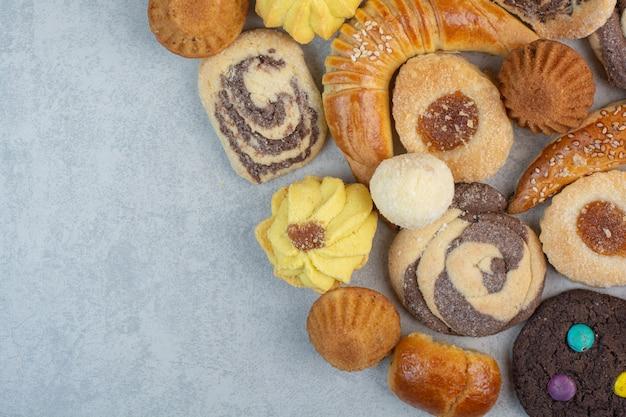 白いテーブルの上の新鮮なおいしいクッキーのいくつか。 無料写真