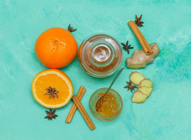 ソーサー、生姜、シアンのテクスチャサーフェス上のスライスにジャムといくつかのオレンジ、上面図。 無料写真