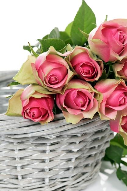白い背景の上のバスケットのいくつかのピンクのバラ 無料写真