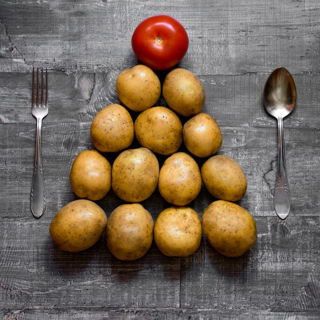 Some potatoes and a tomato on an old wooden table or wooden surface is laid out in the shape of a christmas tree. layout top view Premium Photo