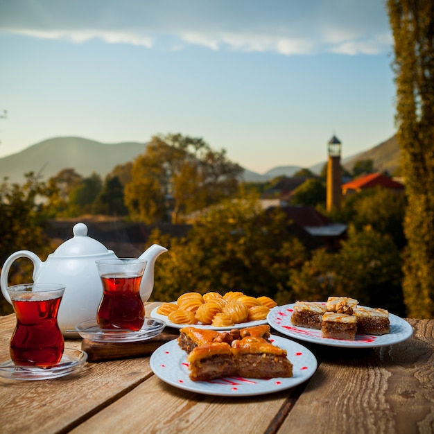 Some turkish desserts with glasses of tea and teapot on a table with village on background, side view. Free Photo