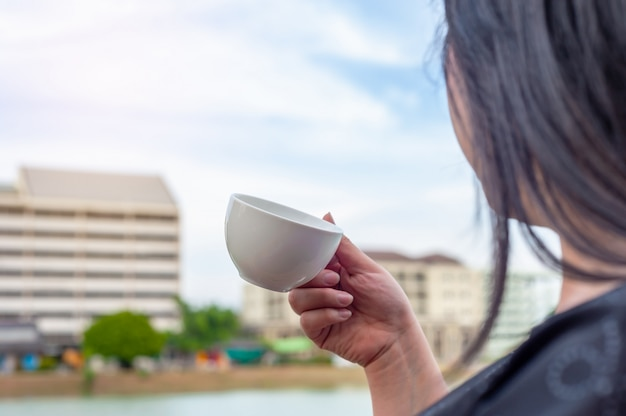 Some women with coffee cup on tower building blurred Premium Photo