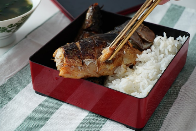 Someone hand using chopsticks trying to pick a grilled saba or mackerel fish served with cooked rice in square bento box on white and green striped placemat on white table Premium Photo